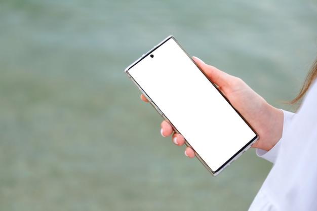 여성 손에 흰색 모형 스마트폰입니다. 여자는 휴대 전화를 사용하여 인터넷에서 검색하고 앱 외부에서 검색합니다. 바다 물 표면에서 스마트폰으로 근접 촬영 여성 손입니다. 복사 공간을 비웃습니다.