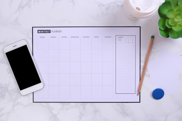 White mockup smartphone and planner schedule on marble background