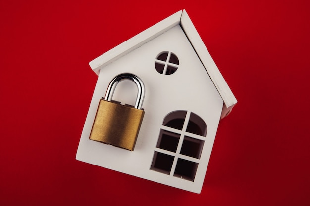 White model of house with lock shut off on red background alarm and security concept