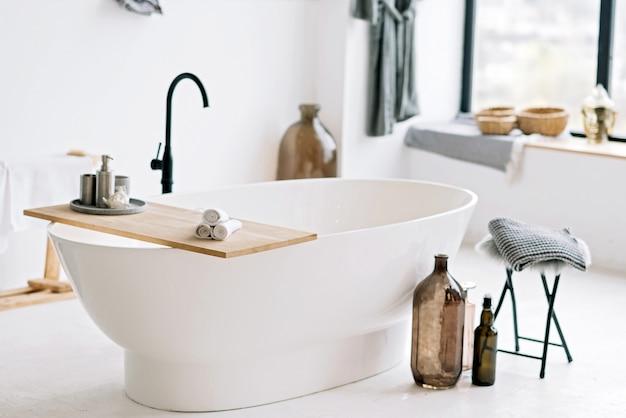 Белая современная ванна в современной квартире со стильным дизайном интерьера в стиле лофт, домашним декором. мягкий выборочный фокус.