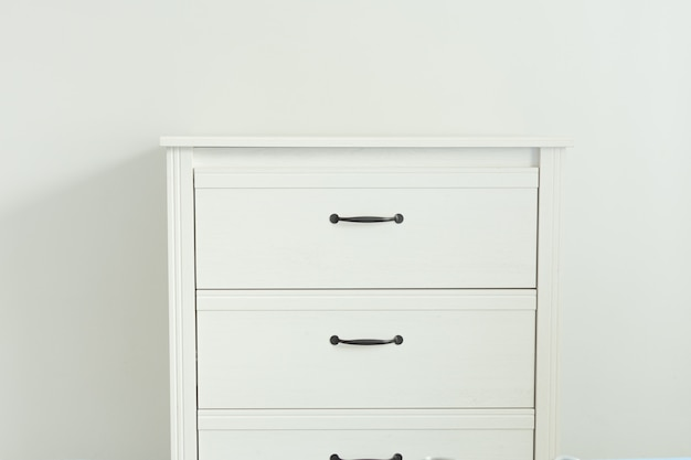 White modern chest of drawers near white wall.