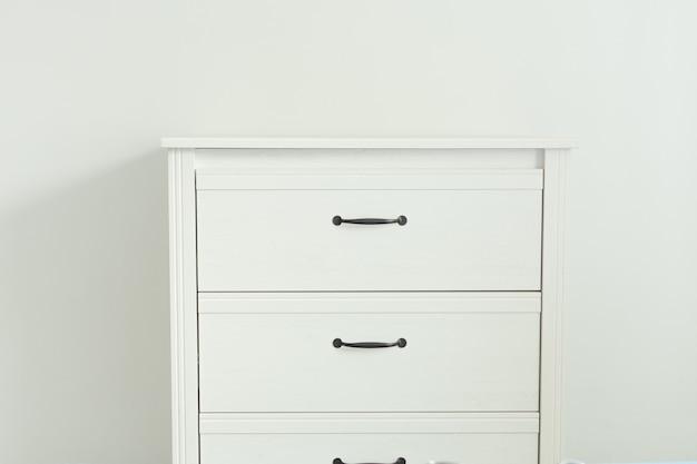 흰 벽 근처 흰색 현대 서랍입니다.