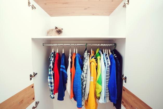 내부에 흰색 현대적인 옷장입니다. 스토리지 조직. 질서와 청결. 집 옷장에 다른 옷이 있는 옷걸이. 옷걸이에 아동복.