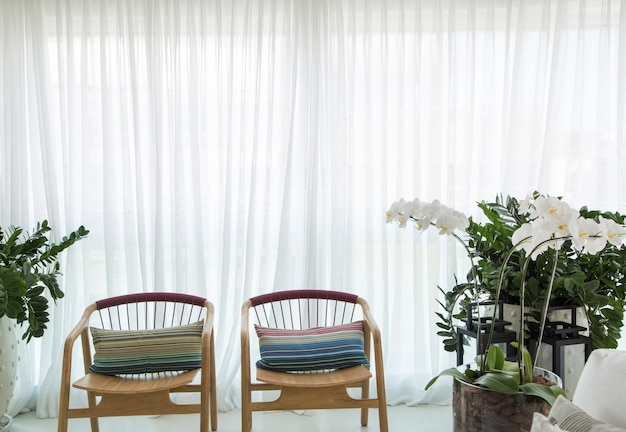 Белый современный интерьер с панорамными окнами и стульями и предметами декора