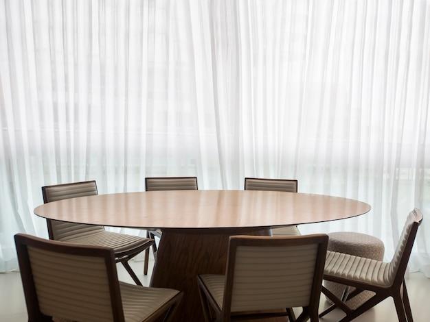 Белый современный интерьер с панорамными окнами и декоративным столом
