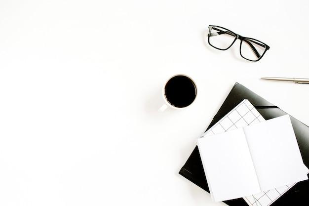 白い表面に空白のノートブック、コーヒー、グラスと白いモダンなオフィスワークスペース