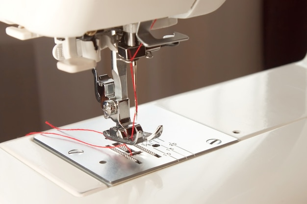 White modern sewing machine presser foot and needle with red thread