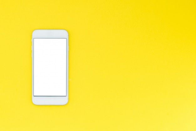 White modern smartphone on a yellow background. flat lay