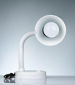 Белая современная настольная лампа, изолированные на белом столе на градиент фона. настольная лампа для чтения книг в общем номере. мебель для дома и офиса с минималистским дизайном. настольный прожектор.