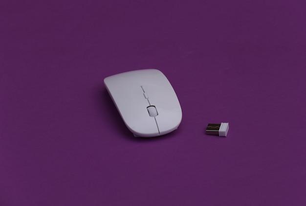 紫色の背景に白いモダンなワイヤレスpcマウス。