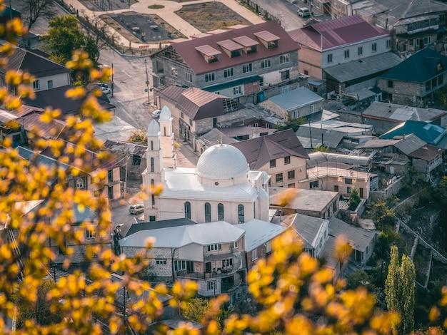 山間の村の中心にある白いモスク。グニブの空中風景と街並みの田園地帯。ダゲスタン。