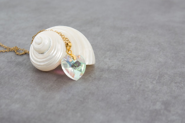 A white mother-of-pearl shell with a beautiful heart-shaped necklace and a beautiful precious stone