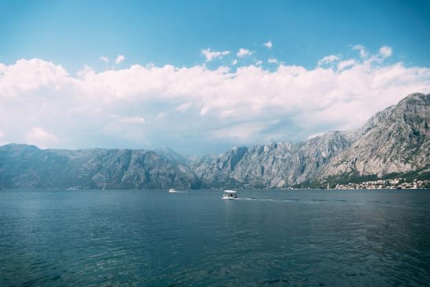 白いモーターボートがコトル湾に沿って山に向かって航行しています