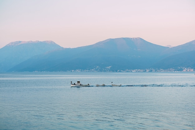 White motor boat tows small rowboats on the sea along the mountains at sunset