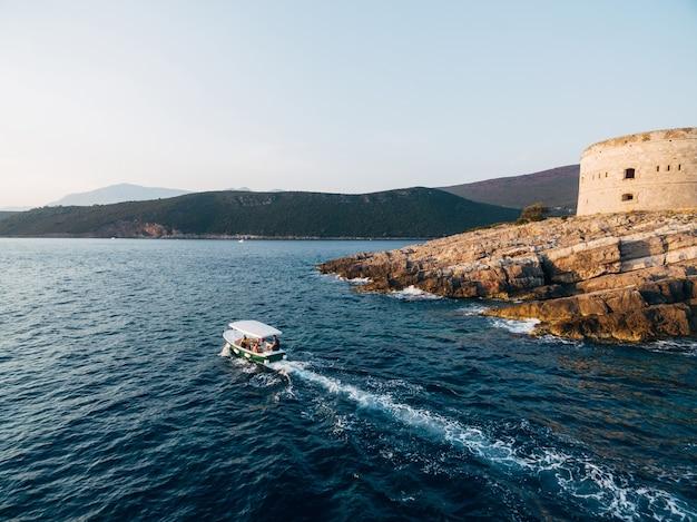 Белая моторная лодка с навесом возит туристов вдоль побережья