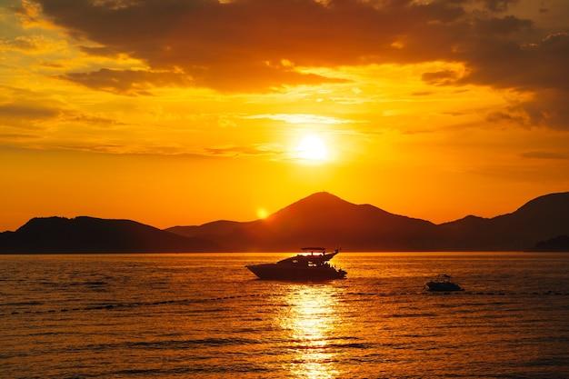 화이트 모터 요트 해질녘 산에 대하여 바다에 항해 프리미엄 사진