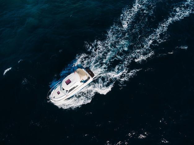 Белая моторная лодка плывет по открытому морю сверху
