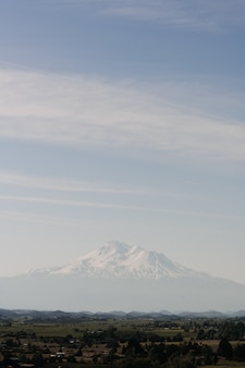 澄んだ空の下で町の近くの白い山