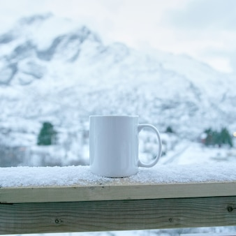 White mug against the background of snow capped mountains