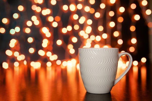 White mug on the dark brown table and background with golden bokeh