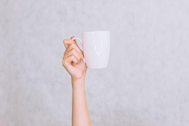 コーヒー用の白いマグカップ、女の子の手にお茶。白い背景に。