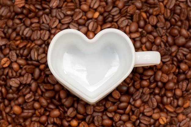 Белая кружка сердце на фоне кофейных зерен