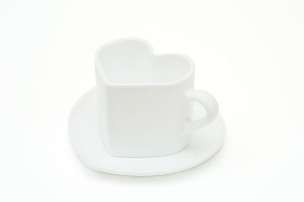 Белая кружка в форме сердца на блюдце на белом фоне