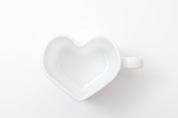 Белая кружка в форме сердца на белом фоне вид сверху