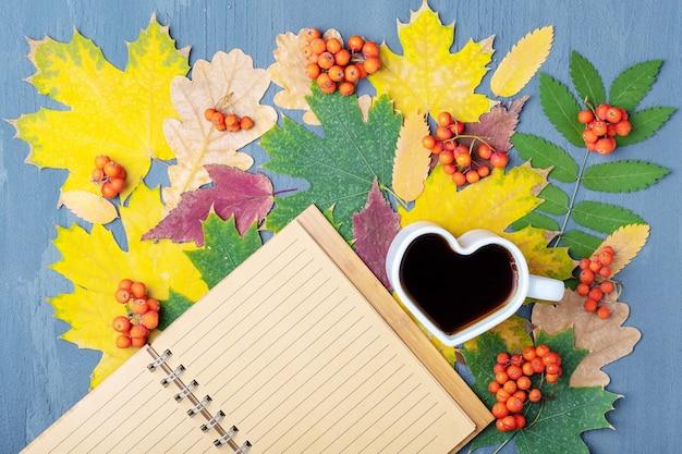 커피 또는 차가 있는 하트 모양의 흰색 머그와 가을 낙엽, 꼭대기 전망, 평평한 바닥에 빈 줄 지어 공예 메모장이 있습니다. 가을 학생 또는 사무실 아침 식사.