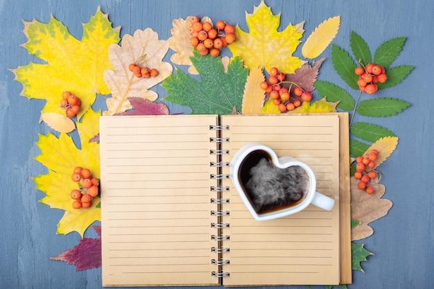 하트 모양의 흰색 머그컵에는 김이 나는 커피나 차, 그리고 가을에 떨어진 마른 화려한 잎의 배경에 빈 줄 지어 공예품 메모장이 있습니다. 가을 아침식사. 근무일 계획