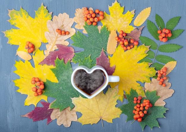 가을 낙엽과 오렌지색 마가목 열매를 배경으로 김이 나는 커피나 차를 넣은 하트 모양의 흰색 머그. 가 블루스 개념입니다. 가을 우울증.