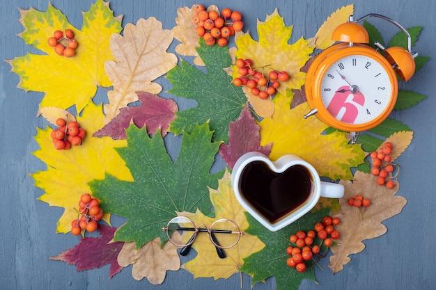 ハートの形をした白いマグカップに、蒸しコーヒーまたは紅茶、オレンジ色の目覚まし時計、秋の乾燥した色とりどりの葉のグラス。朝食の時間。コーヒーを飲む時間。就業日の計画