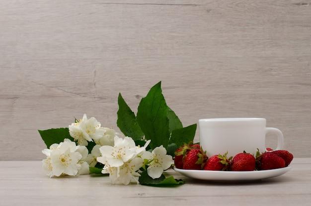 Белая кружка, цветы жасмина и клубника на фоне дерева