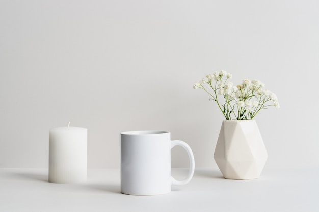 White mug mockup with beige vase, candle and gypsophila branch on a table