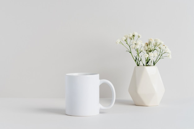 White mug mockup with beige vase and gypsophila branch on a table