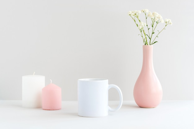 White mug mockup with candles, pink vase and gypsophila branch on a table
