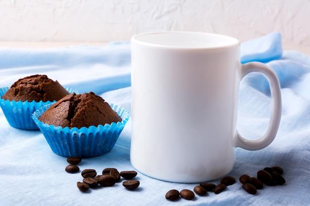 コーヒー豆と2つのチョコレートマフィンと白いマグカップモックアップ