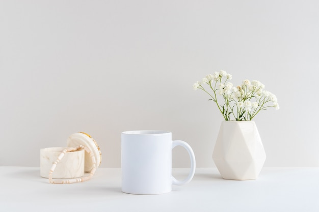 White mug mockup with marble jewelry box, beige vase and gypsophila branch on a table