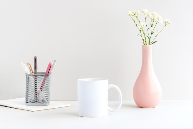 White mug mockup with stationery, pink vase and gypsophila branch on a table