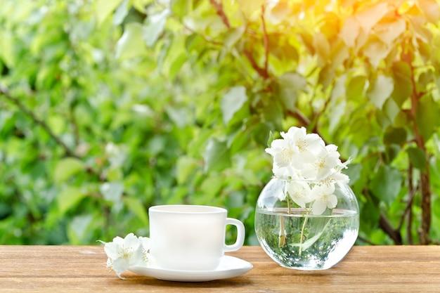 Белая кружка чая и ваза с жасмином. зелень на фоне, солнечный свет