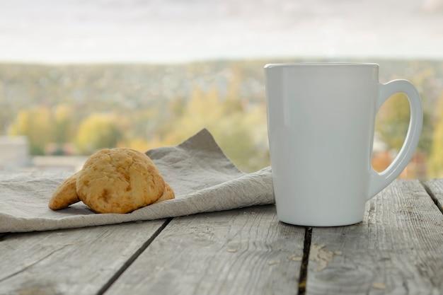 Белая кружка на деревянном столе с печеньем на льняной салфетке