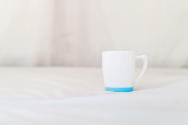 Белая кружка на кровати