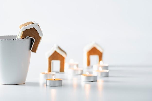 白いマグカップ、小さなジンジャーブレッドハウスとキャンドル。クリスマスの居心地の良い休日。