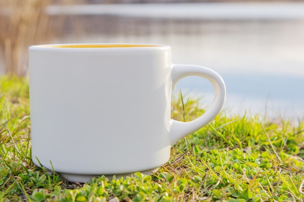 A white mug stands on the grass by the river.