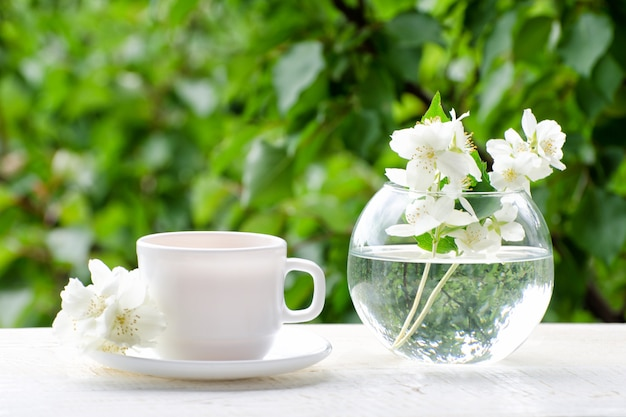 White mug of tea and a vase with jasmine on a wooden table, greens on the background