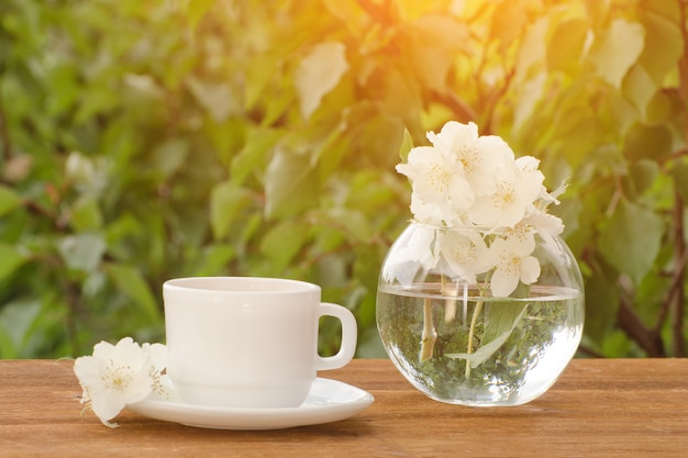 White mug of tea and a vase with jasmine on a wooden table, greens