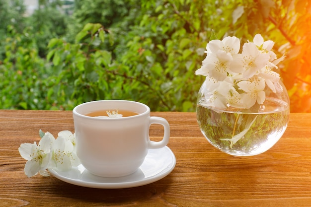 White mug of tea and a vase with jasmine on a wooden table