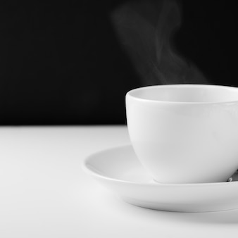 White mug for tea with a hot drink on a white wooden table on a black background.
