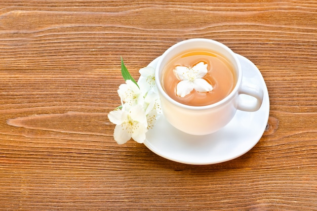 White mug of tea with jasmine on a brown wooden table. close up, top view
