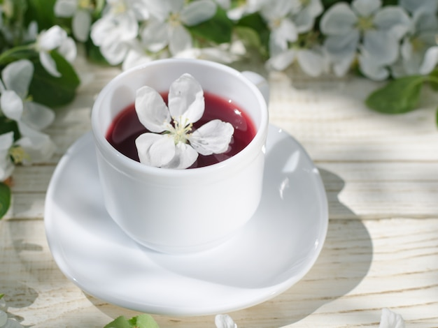 White mug of tea on a wooden table, apple blossoms in the background